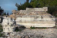 A detail of Roman remains, on 16 April 2007 in Corinth, Greece. A fragment of an inscription mentioning Caesar and a Corinthian capital, lit by the early morning light, lie amongst the ruins of Corinth.  Founded in Neolithic times,  Corinth was a major Ancient Greek city, until it was razed by the Romans in 146 BC. Rebuilt a century later it was destroyed by an earthquake in Byzantine times.