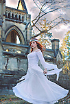 Twirling girl with red hair in front of a large castle wearing a stunning white wedding dress