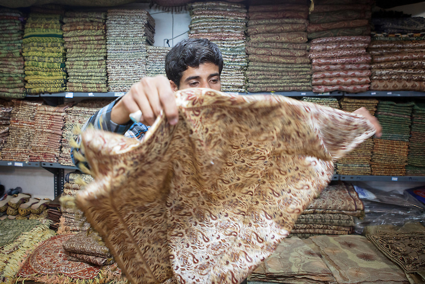 A seller shows his collection of termeh or tirma, the Yazd local silk weaving at his shop at Yazd Old City. During the heyday of the Silk Road, Yazd is a very important city of this ancient trade route. The production of silk in Yazd also well remarked by Marco Polo who visited it 1272.