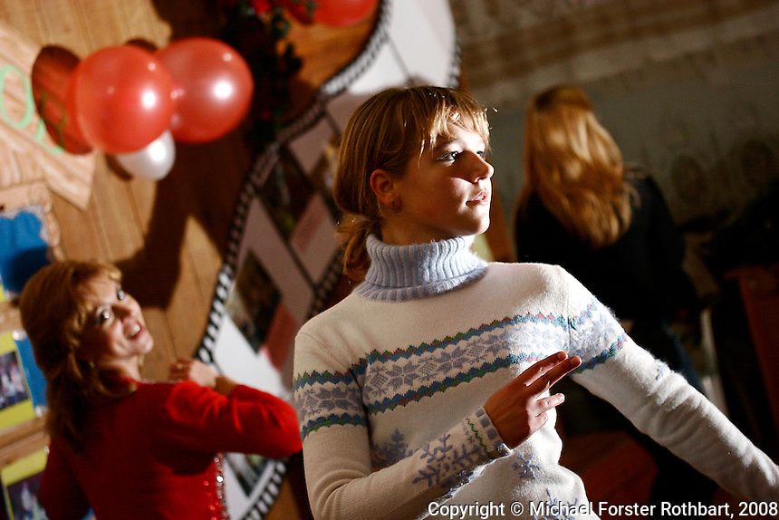 Dance and music teacher Lesya Kostenko (left) leads a dance rehearsal at the Chernobyl Community Center in Borodyanka, Ukraine. Her students, 14-year-olds Ira Dovstenka and Olya Shvitka, are from the resettlement village Nove Zalissya.  <br /> ------------------- <br /> This photograph is part of Michael Forster Rothbart's After Chernobyl documentary photography project.<br /> &copy; Michael Forster Rothbart 2007-2010.<br /> www.afterchernobyl.com<br /> www.mfrphoto.com <br /> 607-267-4893 o 607-432-5984<br /> 5 Draper St, Oneonta, NY 13820<br /> 86 Three Mile Pond Rd, Vassalboro, ME 04989<br /> info@mfrphoto.com<br /> Photo by: Michael Forster Rothbart<br /> Date:  10/2008    File#:  Canon 20D digital camera frame 10694 <br /> ------------------- <br /> Original caption: .Dance and music teacher Lesya Kostenko leads a dance rehearsal at the Chernobyl Community Center in Borodyanka, Ukraine. Her students, Ira Dovstenka (in white), Olya Savechenko (singing) and Olya Shvitka (in black) are all 14-year-old girls from the village Nove Zalissya, 7 kilometers away. Borodyanka is a small town (population 16,000) 30 miles west of Kyiv and 48 miles south of the Chernobyl nuclear power plant, where many Chernobyl evacuees were resettled in 1986..-------------------.