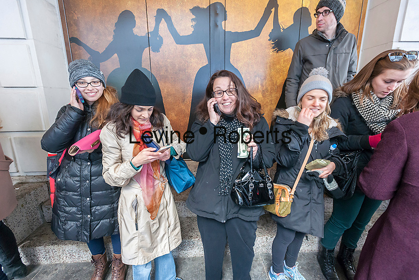 "Winners line up with their cash at the Richard Rodgers Theatre in Times Square in New York on Wednesday, April 6, 2016 after their names are called for tickets in the #Ham4Ham lottery for seats for the Broadway blockbuster ""Hamilton"". The $10 live lottery takes place in front of the theater for the Wednesday matinee performance while for the rest of the week's performances the lottery is online. (© Richard B. Levine)"