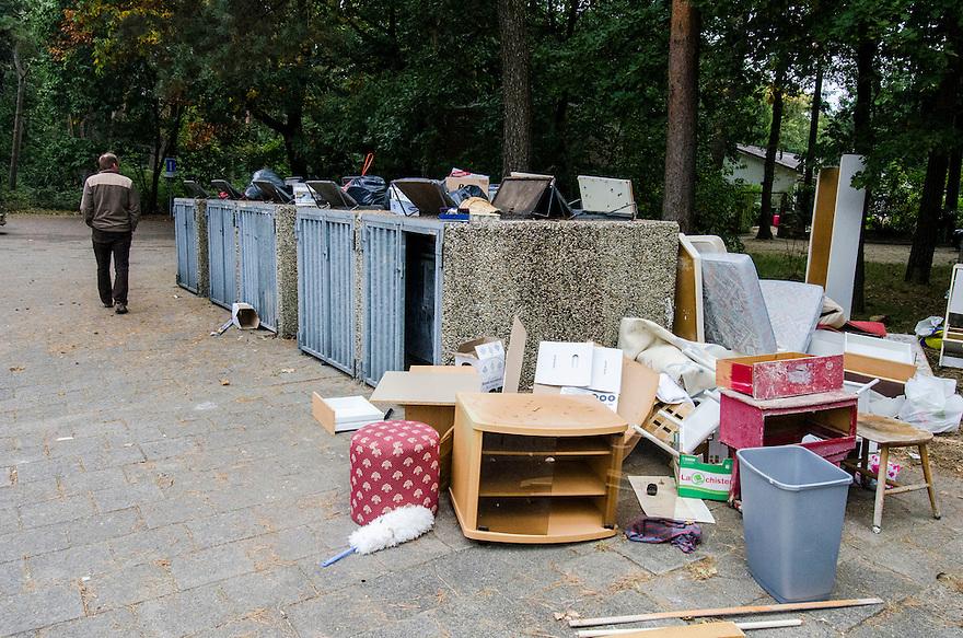 Nederland, Zeist, 22 sept 2014<br /> Afvalcontainers bij een flat die gesloopt gaat worden. Bewoners moeten uit hun huizen en gooien heel veel huisraad weg, vandaar de rommel naast de afvalcontainers voor het normale huisvuil<br /> Foto: (c) Michiel Wijnbergh