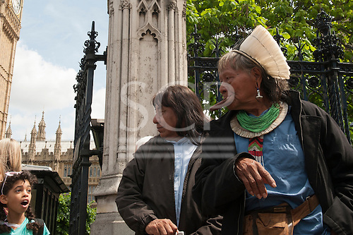 11 June 2014. Kayapo Chiefs Raoni Metuktire and Megaron Txucarramae during their visit to London. The chiefs stand in front of the British Houses of Parliament in Westminster; a surprised young girl stands looking at them with her mouth open.