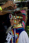 Close up of youngNative American boy being helped by mother for  Pow Wow Regalia. Examples of ethnic pride, heritage, celebration, and traditional folk art crafts