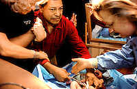 "Medical staff and interpreters guide an excited Roy Rios in cutting the umbilical cord of his new daughter, Shanice Morgan-Rios.  ""I hope my baby is not born deaf-blind with Usher's syndrome, like me,"" said Rios, who is deaf-blind and has three other siblings with the disease.  Usher's is hereditary.; there is no trreatment or cure.  Rios already has a son, who was born without Usher's.  Tests show that his daughter is able to hear.  Doctors will test her later to determine whether she has any vision problems."