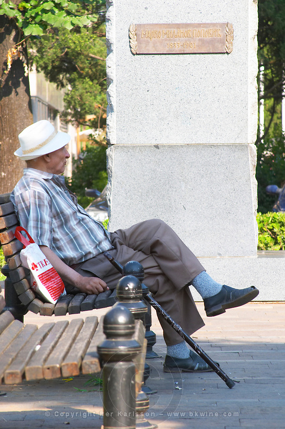 an old man with a walking stick sitting on a bench Podgorica capital. Montenegro, Balkan, Europe.