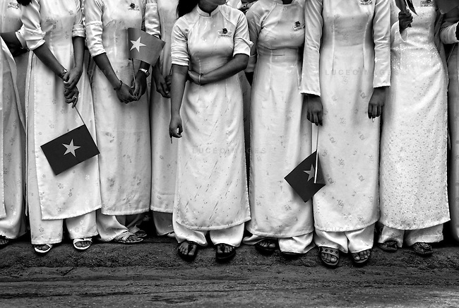 Communist flags contrast the monochromatic traditional dresses called, ao dai, as Vietnamese students line the streets of Hoi An, Vietnam, during a parade for visiting Chinese delegates.