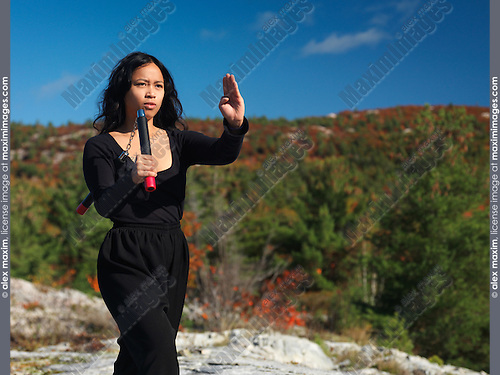 Portrait of a young asian woman martial artis practicing nunchucks in the nature. Ontario, Canada.