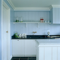 In the kitchen of an 18th century Dutch house the tongue and groove panelling is painted a light blue in a cool contrast to the black granite work surface
