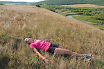 Young female runner laying in the sun on a grassy field above the Little Saskatchewan River in Manitoba, Canada relaxing.