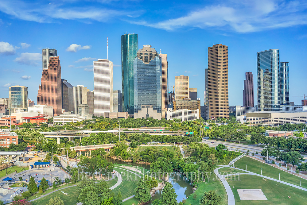 This is a aerial view of the Houston Skyline with the Buffalo Bayou, Elenor Tinsley Park and the Jaimal Skate Park all in the image below. You can also see the Sabine St. Bridge along with the Allen Parkway and on the other side is Memorial dirve running along the other side of the park.  The city view includes the usual skyscrapers like the Chase Tower, Heritage Plaza, Wells Fargo, and the 1400 Smith St. buildings just to name a few.  You can see the Houston City Hall building at the base of the buildings where it is dwarfed by the high-rise skyscrapers since Houston has some ot the tallest buildings in the southern US.