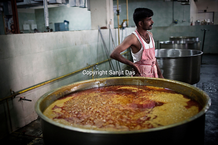 A chef is seen preparing meals in the kitchen of the Sai Prasadalaya in Shirdi, Maharashtra, India. The Prasadalaya feeds an approximate number of 30000 Sai Baba devotees as a Prasad (holy meal) every day. Free Prasad meals are served to all the devotees. An approximate number of 1000 devotees are served everyday with this facility. Expenses for a plate of Prasad meal  is around Rs. 15/- but the Saibaba Sansthan provides prasad meals to all Sai devotees to Rs. 6/- only. The prasadalaya at the Shirdi Sai Baba Shrine is powered by a large array of concave mirrors that transform sunlight to energy to create hot water and steam for the cooking process. Photograph: Sanjit Das