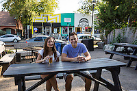 Attractive young couple enjoying beer on a date during warm summers night in East 6th Street, East Austin, Austin's hip and happening entertainment district.