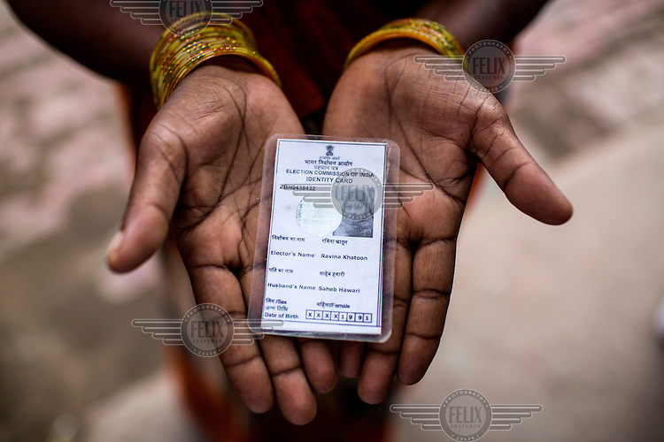 A woman holds the only photograph of Ravina Khatoon from Shivpur Hariyya village who died a few days after giving birth.