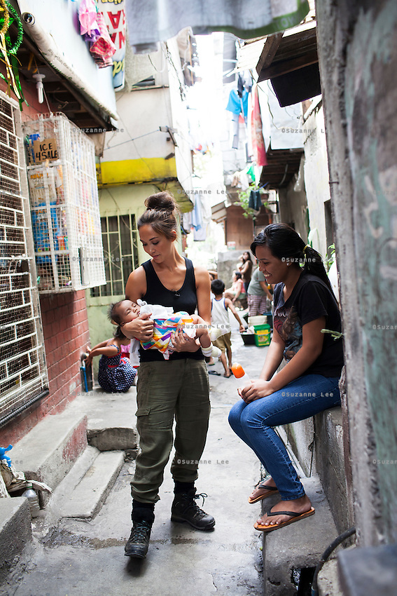 Myleene Klass (left), a celebrity from the UK, meets single mother Josephine Savares, 18, as she holds her 1st child Jihan, aged 4 months, in her neighbourhood, in Paranaque City, Metro Manila, The Philippines on 19 January 2013. After watching advertisements, Josephine had decided to feed her baby formula during her pregnancy and had no idea that her father had to pay such a high price for it. Her family goes without food some days, and her siblings have had to stop school in order to afford the formula. Photo by Suzanne Lee for Save the Children UK