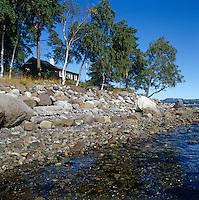 The log cabin backs onto the rocky shore and crystal clear water of the fjord near Oslo