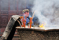 worker in Chinese buddhist shrine in the city of Shanghai China