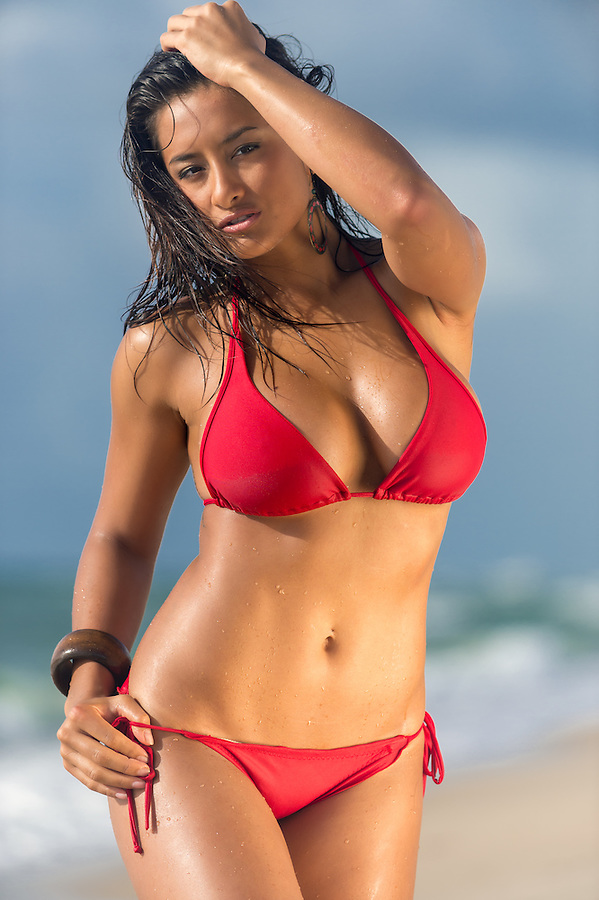 Portrait of hot female in red bikini posing over the blurred beach background