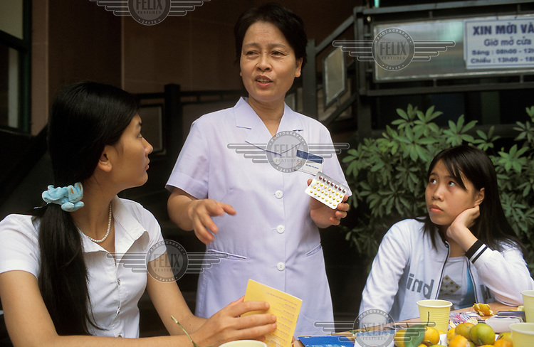 A doctor and counsellor holds up contraceptive pills during a sexual health education programme for female university students.