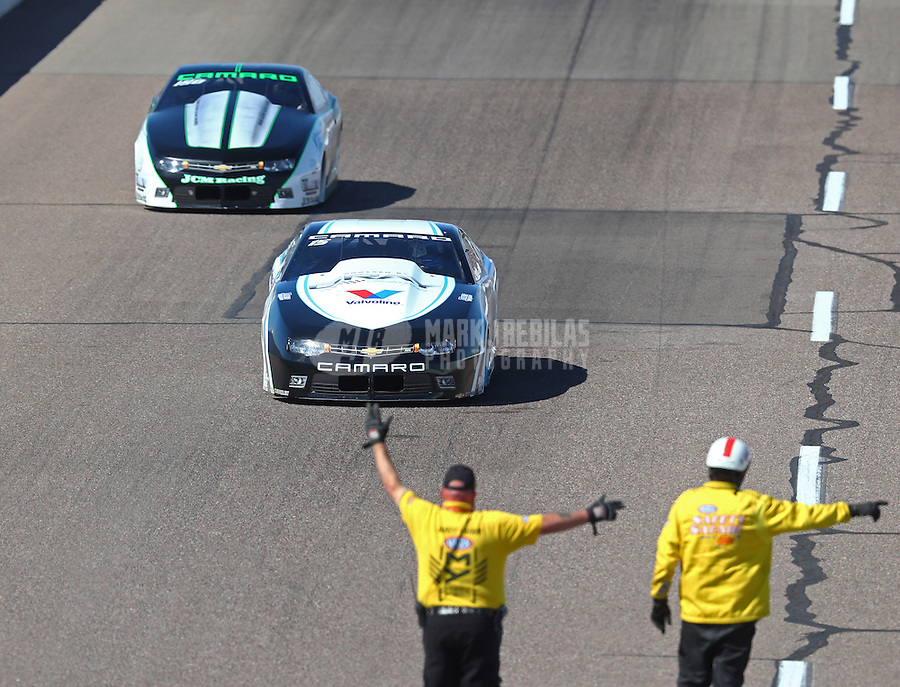 Feb 25, 2017; Chandler, AZ, USA; NHRA safety safari member directs pro stock drivers Tanner Gray and Kenny Delco off the track during qualifying for the Arizona Nationals at Wild Horse Pass Motorsports Park. Mandatory Credit: Mark J. Rebilas-USA TODAY Sports