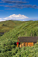 Man stands on a porch of a log cabin, Mt. McKinley (locally called Denali) in the distance, Denali National Park, Alaska.