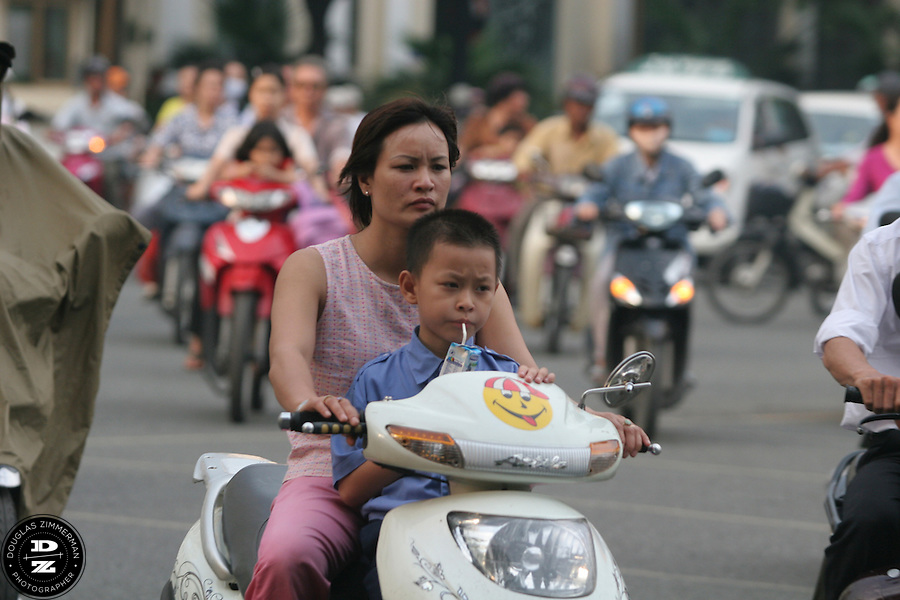 A mass of motorbikes drives along DL Nguyen Hue in Ho Chi Minh City, Vietnam.  Motorbikes are used by families of all sizes throughout Vietnam for transportation and other purposes.  Photograph by Douglas ZImmerman
