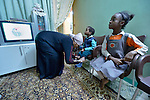 Mona Ahmed, a refugee from the Darfur region of Sudan, helps her son Ahmed, 4, get dressed for school as her daughter Dana, 7, watches television in the family's crowded apartment in Cairo, Egypt. She and her husband have both taken adult education classes provided by St. Andrew's Refugee Services, which is supported by Church World Service.