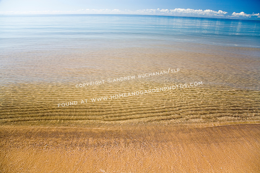 Ripples in the underwater sand along the shoreline of Lake Huron, in the eastern Upper Peninsula of Michigan with a blue summer sky and puffy white clouds above the distant curving horizon.