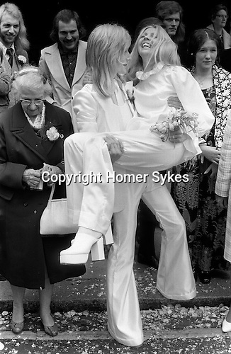 Caxton Hall Westminster London. Londons main register office untill 1979. White wedding his and her uni sex clothes, trouser suits, flares or bell bottoms, and cuban healed shoes. Long hair. 1970s fashionable London...He is Michael Stephens I think a well know hairdresser of the time.
