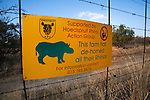 Sign on game farm perimeter fence to deter rhino poachers explaning rhinos there have been dehorned, Hoedspruit, Limpopo, South Africa, June 2012