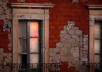 Detail of a ruined red facade with a window reflecting the sunrise in Ortigia, Syracuse, Sicily, pictured on September 14, 2009, in the morning. The The 2,700 year old Syracuse is a province and a city in southern Italy on the Island of Sicily. The island Ortigia is the historic centre of Syracuse. Today the city is a UNESCO World Heritage Site. Founded by Ancient Greek Corinthians and allied with Sparta and Corinth, it was a very powerful city-state and one of the major powers of the Mediterranean.  In the 17th century it was heavily destroyed by an earthquake. Many buildings date back to the  19th century when it regained importance. Picture by Manuel Cohen.