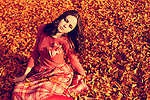 A pretty brunette dressed in pink vintage clothing sitting in fallen orange leaves.