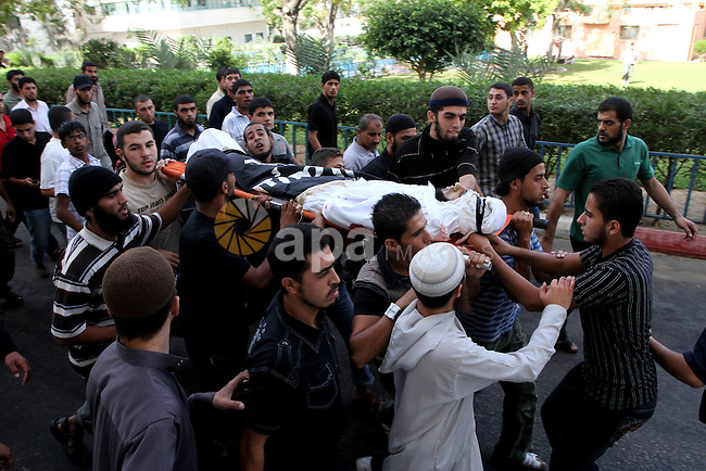 Palestinian mourners carry the body of militant Mahmud Washa during his funeral at the Shati refugee camp in Gaza City on October 17, 2010. Two Palestinians were killed and a third wounded in the pre-dawn Israeli air strike north of Gaza City, Palestinian medics said . Photo by Ashraf Amra