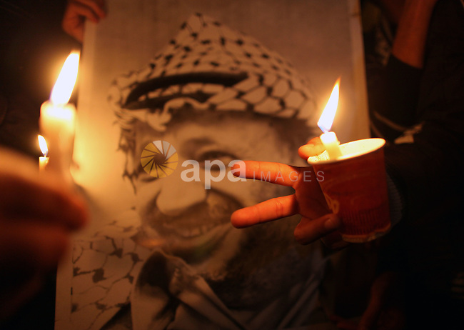 Palestinians hold candles and pictures of late Palestinian leader Yasser Arafat during a ceremony marking the seventh anniversary of his death in Gaza City on November 13, 2011. Photo by Mahmud Nassar