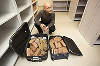 "Switzerland. The Republic and Canton of Neuchâtel. Neuchâtel. The commissar Manuel Garcia at the police station headquaters. The narcotics squad during ""Narko"" operation has seized two luggages full of cannabis (6 kg) and hashich (21 kg). The narcotics squad works in plainclothes. Plainclothes law enforcement is a method used by police. The policemen wear plainclothes or ""ordinary clothes"" instead of a uniform in order to avoid detection or identification as law enforcement agents. Cannabis, commonly known as marijuana, is a preparation of the Cannabis plant intended for use as a psychoactive drug. Pharmacologically, the principal psychoactive constituent of cannabis is tetrahydrocannabinol (THC); it is one of 483 known compounds in the plant, including at least 84 other cannabinoids, such as cannabidiol (CBD), cannabinol (CBN), tetrahydrocannabivarin (THCV), and cannabigerol (CBG). Hashish, or hash, is a cannabis product composed of compressed or purified preparations of stalked resin glands, called trichomes. It contains the same active ingredients—such as tetrahydrocannabinol (THC) and other cannabinoids—but often in higher concentrations than unsifted buds or leaves. 31.03.15 © 2015 Didier Ruef"