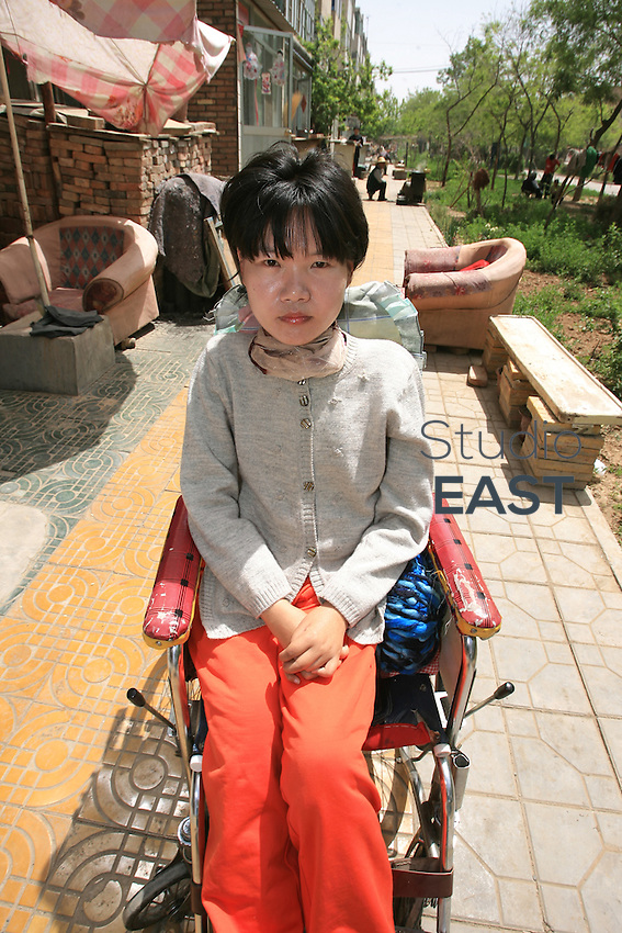Li Yan sits in a wheel-chair in front of her home in Yinchuan, Ningxia Province, China, on May 7, 2007. 28-year-old Li Yan suffers from motor neuron disease also known as amyotrophic lateral sclerosis (or ALS), the same illness that has thereotical physicist Stephen Hawking. Li Yan asked China's National People's Congress (NPC) to consider a draft on euthanasia. Photo by Lucas Schifres/Pictobank