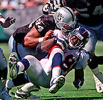 Oakland Raiders vs. Denver Broncos at Oakland Alameda County Coliseum Sunday, September 17, 2000.  Broncos beat Raiders  33-24.  Oakland Raiders defensive end Tony Bryant (94) brings Denver Broncos running back Mike Anderson (38) to the ground.