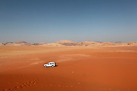 Four-wheeled vehicle in the middle of a wide sandy valley, Wadi Rum Protected Area (WRPA), Wadi Rum National Park, also known as The Valley of the Moon, 74,000-hectare, UNESCO World Heritage Site, desert landscape, southern Jordan, Middle East. Picture by Manuel Cohen