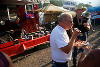 People stand outside the Rock Creek Lodge in Clinton, MT, to socialize, eat, and drink, at the Testicle Festival.  The Rock Creek Lodge in Clinton, MT, has hosted the annual Testicle Festival since the early 1980s.  The four day festival and party revolves around the consumption of so-called Rocky Mountain Oysters, which are deep-fried bull testicles.