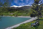 Wooden seat looking towards hamlet/villageLake Resia, Italian/ Austrian border. The Alps.
