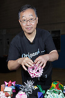 New York, NY, USA - June 24, 2011: Toshikazu Kawasaki, original Origami designer and folder from Japan at the OrigamiUSA Convention in New York City holding his creation, a modular work made of multiple squares of coloured paper.