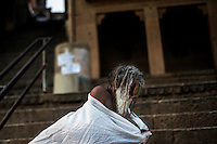A holy man changes cloth after taking bath at a ghat in Varanasi, Uttar Pradesh, India.