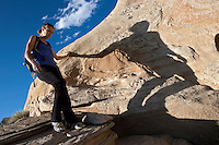 A hiker casts a long, sinuous shadow on a Utah afternoon in Capitol Reef National Park.