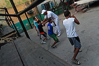 A Cuban boxing coach works with young boys at Rafael Trejo boxing gym in Havana, Cuba, 11 February 2010. During the last 30 years Cuba has produced more World Champions and Olympic gold medallists in amateur boxing than any other country. Many famous fighters, who came out of Cuba, were training at Rafael Trejo boxing gym in their youth. This run down open air facility in the Old Havana is a place of learning and mastering the art of boxing by the old school style. Boys begin their training very young. As sports are given a high political priority in Cuba, all children are systematically encouraged to develop their skills. Those who succeed will become heroes of Cuban society.