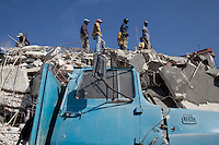 Men stand on top of a building that collapsed in the recent earthquake in Port-au-Prince, Haiti.