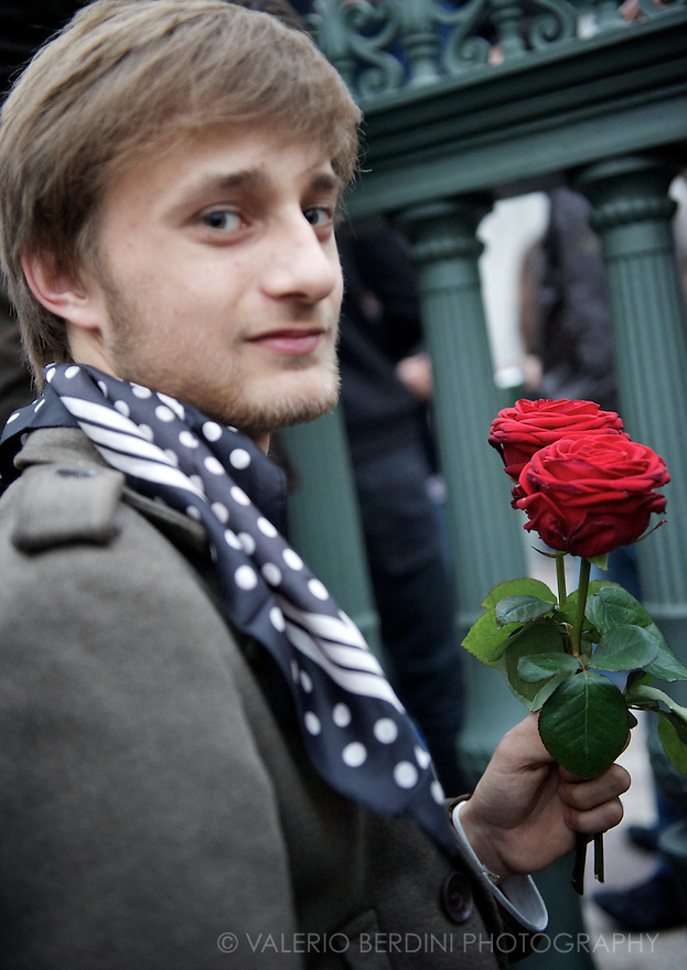A man holds red roses, the symbol and the logo of PS (parti socialiste) of Francois Hollande