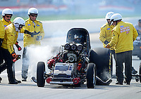Sept 9, 2012; Clermont, IN, USA: NHRA safety safari crews tend to funny car driver Todd Lesenko after blowing the body off his car in a fiery explosion during the US Nationals at Lucas Oil Raceway. Mandatory Credit: Mark J. Rebilas-