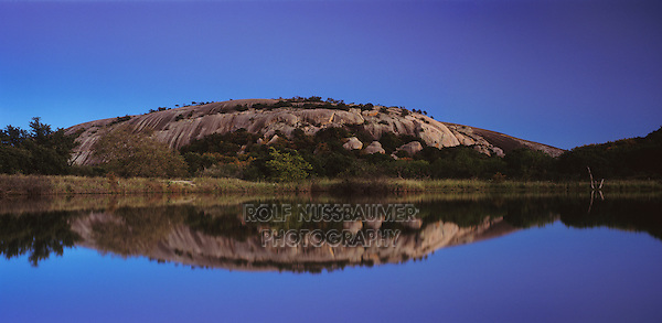 Dome reflecting in pond at dusk, Enchanted Rock State Natural Area, Fredericksburg,Texas, USA