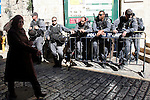 A Palestinian woman walks pass Israeli police officers following the Friday prayers in al-Aqsa mosque, in Jerusalem old city on November 30, 2012. Photo by Mahfouz Abu Turk