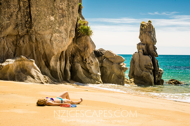 Young woman sunbathing on pristine Anapai Bay with its granite rock formations on Abel Tasman Coast Track, Abel Tasman National Park, Nelson Region, South Island, New Zealand